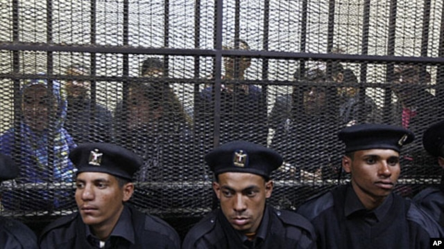 Policemen sit in front of a cage holding Egyptian employees of several pro-democracy groups during court proceedings in Cairo, Egypt, Sunday, February 26, 2012.