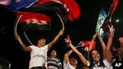 ຜູ້ສະໜັບສະໜູນຂອງປະທານາທິບໍດີ ນິຄາຣາກົວ ທ່ານ Daniel Ortega ແລະ ຜູ້ລົງແຂ່ງຂັນເອົາຕຳແໜ່ງຮອງ ປະທານາທິບໍດີ, ພັນລະຍາຂອງທ່ານ, ທ່ານນາງ Rosario Murillo ແກວ່ງທຸກພັກແນວໜ້າປະຕິວັດສັງຄົມນິຍົມແຫ່ງຊາດ ຫຼື FSLN ໃນຂະນະທີ່ທ່ານ Ortega ໄດ້ຊະນະການເລືອກ ຕັ້ງຄືນ, ໃນເວລາທີ່ກຳລັງ ສະເຫຼີມສະຫຼອງໃນນະຄອນຫຼວງ ມະນາກົວ, ປະເທດ ນິຄາຣາກົວ. 6 ພະຈິກ, 2016.