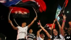 Supporters of Nicaragua's President Daniel Ortega and vice presidential candidate, his wife, Rosario Murillo wave flags of the Sandinista National Liberation Front, or FSLN, as Ortega won re-election, while celebrating in Managua, Nicaragua, Nov. 6, 2016.