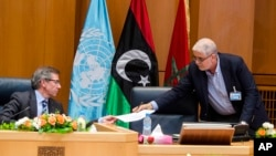 Wakil Khusus PBB untuk Libya, Bernardino Leon (kiri), menerima dokumen dari Mustafa Abushagur, perwakilan pemerintahan Libya yang diakui, dalam pertemuan di Skhirate, Maroko (2/7).