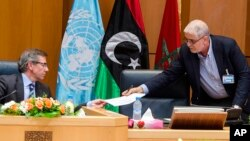 Bernardino Leon, left, the U.N. special envoy to Libya, receives a document from Mustafa Abushagur, a representative of the internationally recognized government that fled to Tobruk, Libya, during a meeting in Skhirate, Morocco, July 2, 2015.