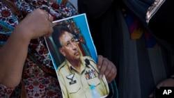 Những người ủng hộ cựu tổng thống Pervez Musharraf cầm ảnh của ông đứng bên ngoài tòa án ở Islamabad, đang xét xử ông, 31/3/14