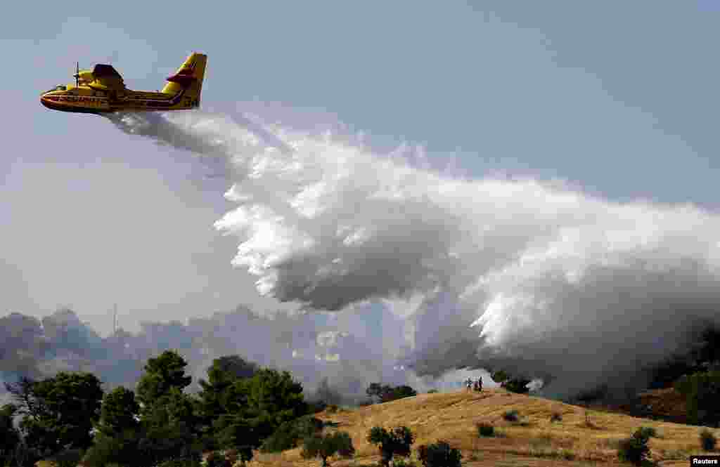 Locals watch as a firefighting plane drops water over a fire near holiday homes in Costa village in the Argolida region, in Southeastern Greece during a developing wild fire.