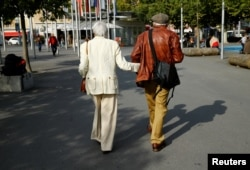 Elderly people walk in the street, ahead of a national vote on pensions reform, in Lausanne, Switzerland, Sept. 22, 2017.