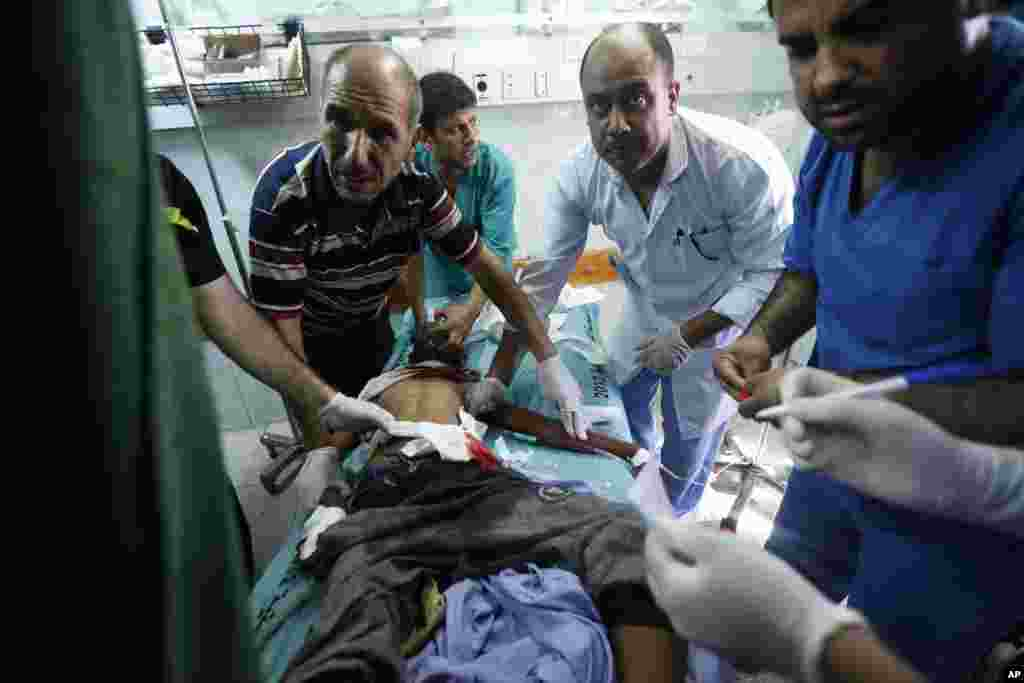 Palestinian medics treat a child wounded in an Israeli strike on a compound housing a U.N. school in Beit Hanoun, in the northern Gaza Strip, at the emergency room of the Kamal Adwan hospital in Beit Lahiya, July 24, 2014.