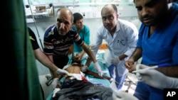 Nhân viên cấp cứu Palestine chăm sóc cho một trẻ em bị thương trong vụ oanh kích của Israel