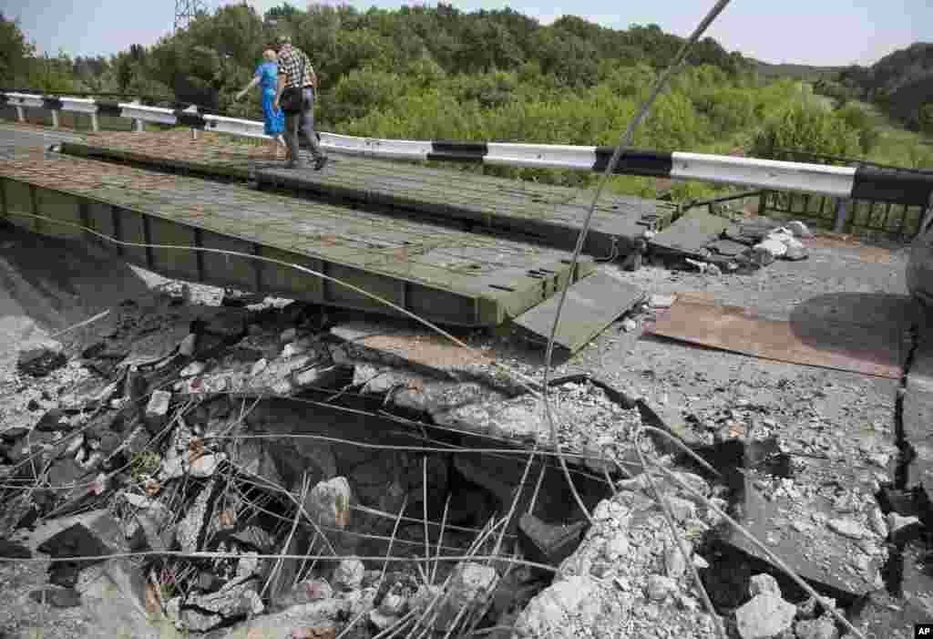 People walk across a heavily damaged bridge near the village of Debaltseve, Donetsk region, July 31, 2014.