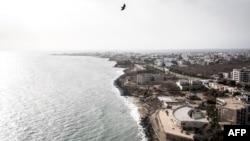 Des gens se baignent sur les plages populaires des Mammelles, devant des chantiers à Dakar, le 27 juin 2020.