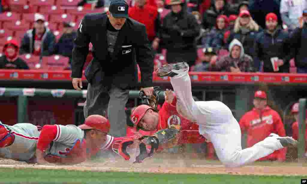 Tucker Barnhart នៃក្រុមCincinnati Reds ទទួលពិន្ទុទ្វេរខណៈពេលលោក Carlos Ruiz អ្នកចាប់នៃក្រុម Philadelphia Phillies ព្យាយាមចាប់ក្នុងឱកាសទី៣នៃកីឡាបេស្បល ក្រុងCincinnati រដ្ឋOhio។