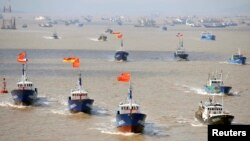 Fishing boats are seen departing from Shenjiawan port in Zhoushan, Zhejiang province towards the East China Sea fishing grounds, September 17, 2012.