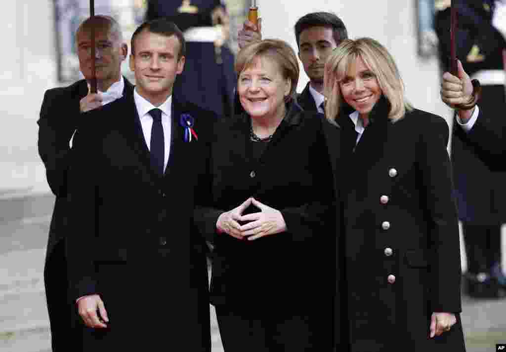 German Chancellor Angela Merkel, center, is greeted by French President Emmanuel Macron and his wife Brigitte Macron as she arrives at the Elysee Palace in Paris to participate in a World War I Commemoration Ceremony, Nov. 11, 2018.