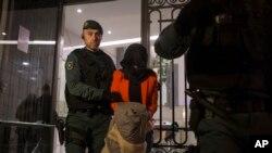 西班牙国民警卫队的一名警察将一名被拘押的女子带离中国工商银行在马德里的办事处。(2016年2月17日)