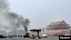 FILE - Vehicles travel along Chang'an Avenue as smoke raises in front of a portrait of late Chinese Chairman Mao Zedong at Tiananmen Square in Beijing, Oct. 28, 2013.
