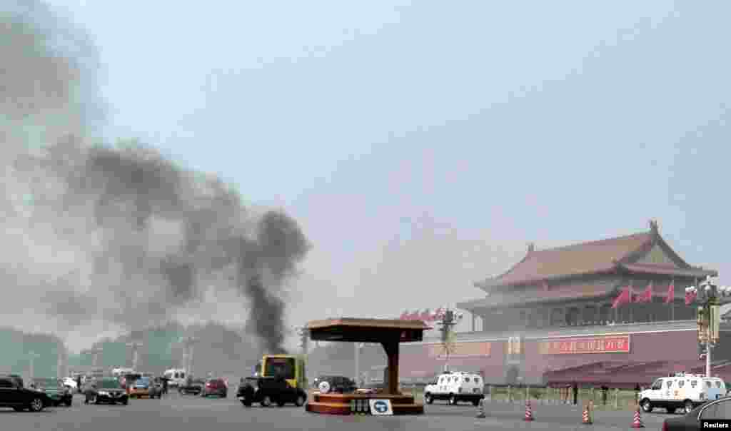 Vehicles travel along Chang'an Avenue as smoke raises in front of a portrait of late Chinese Chairman Mao Zedong at Tiananmen Square in Beijing.