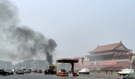 Vehicles travel along Chang'an Avenue as smoke raises in front of a portrait of late Chinese Chairman Mao Zedong at Tiananmen Square in Beijing, Oct. 28, 2013.
