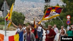 "FILE - Buddhist monk Thubten Wangchen (3rd R) and participants walk with Tibetan flags and images of Mahatma Gandhi during their march for ""peace and non-violence"" from Plaza d'Espanya [Spain Circus] to the Montjuich castle in Barcelona, Oct. 2, 2010."