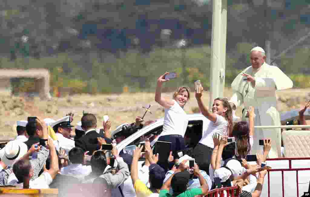 Pope Francis waves to the crowd as he rides in the popemobile through Samanes Park, where he will celebrate Mass, in Guayaquil, Ecuador.
