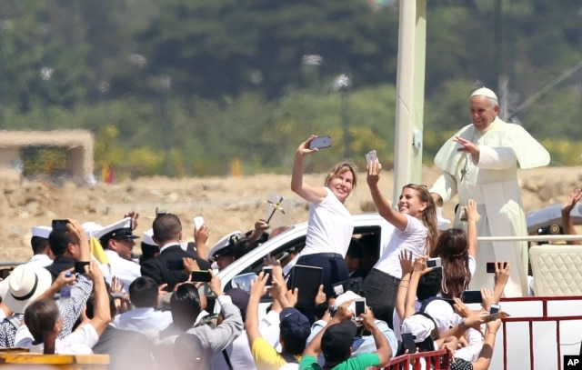 FILE - Pope Francis waves to the crowd as he rides in the popemobile through Samanes Park, where he will celebrate Mass, in Guayaquil, Ecuador, July 6, 2015.