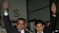 ທ່ານ Jatuporn Prompan, (ຂ້າງຊ້າຍ) ແລະທ່ານ Nisit Sinthuprai,(ຂ້າງຂວາ) ຜູ້ນໍາພວກເສື້ອແດງ ພັກຝ່າຍຄ້ານ ພາກັນຍົກມືຂຶ້ນໃນຫ້ອງຂັງໃນສານອາຍາ ທີ່ບາງກອກ ວັນທີ 12, ພຶດສະພາ 2011.