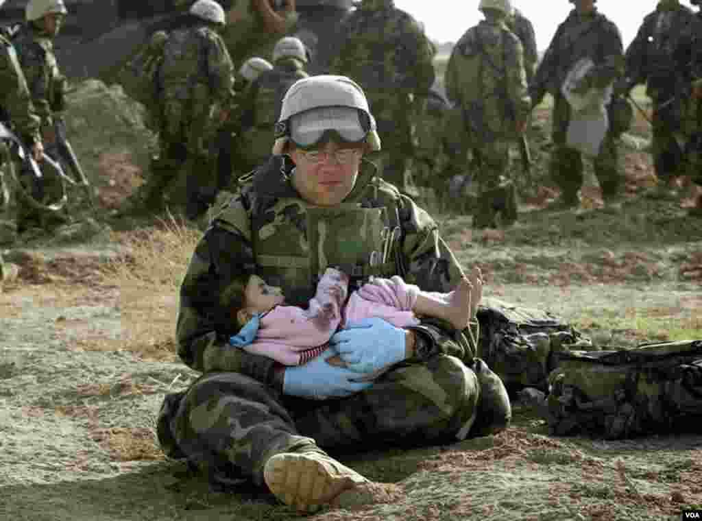 Birinci Dəniz Piyadaları Diviziyasında xidmət edən ABŞ Donanma hospital korpusmeni Richard Barnett mərkəzi İraqda uşağı qucağında tutub. (29 mart, 2003). Döyüş zamanı uşaq ailəsindən ayrı düşmüşdü. Foto: Damir Sagolj via Business Insider.