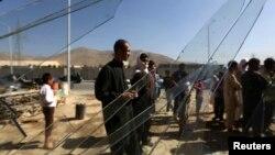 Warga di balik kaca jendela yang pecah di lokasi pemboman di luar kantor pemberantasan narkoba dekat bandara Kabul (22/7). (Reuters/Omar Sobhani)
