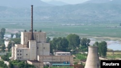 A North Korean nuclear plant is seen before demolishing a cooling tower (R) in Yongbyon, in this photo taken June 27, 2008 and released by Kyodo.