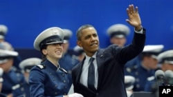 President Obama waves as he congratulates a cadet during the graduation ceremony at the United States Air Force Academy in Air Force Academy, Colo., Wednesday, May 23, 2012. (AP Photo/David Zalubowski)