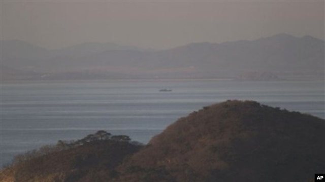 A North Korean ship passes between the North Korean mainland, background, and the South Korean island of Yeonpyeong, foreground, 26 Nov 2010