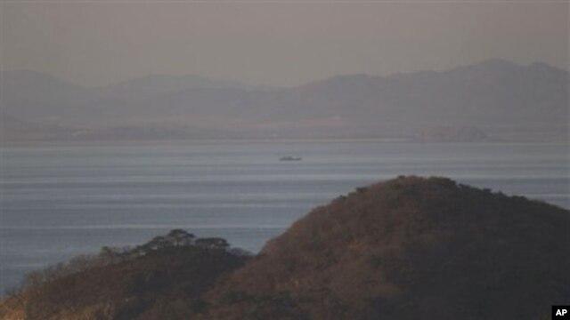 A North Korean ship passes between the North Korean mainland, background, and the South Korean island of Yeonpyeong, foreground, 26 Nov 2010