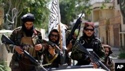 FILE - Taliban fighters display their flag on patrol in Kabul, Afghanistan, Aug. 19, 2021.
