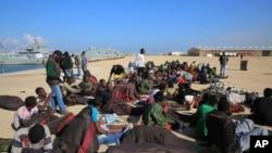 Photo d'archives: Des migrants africains se reposent après avoir été secourus par les garde-côtes libyennes, à l'ouest de Tripoli, Libye, le lundi 21 décembre 2015.