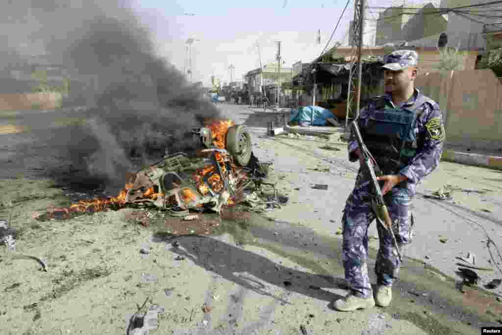 A policeman stands guard at the site of a bomb attack in Kirkuk, north of Baghdad, Iraq, July 23, 2012.