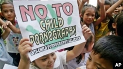 Filipino children show signs against child pornography during the start of a nationwide alliance to combat the growing problem in the Philippines.