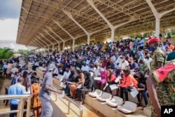 FILE - People wait in the stands to receive coronavirus vaccinations at the Kololo airstrip in Kampala, Uganda, May 31, 2021.