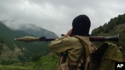 FILE - A Pakistani militant holds a rocket-propelled grenade in Shawal, in Pakistan's tribal region of Waziristan, Aug. 5, 2012. Two former al-Qaida members have reportedly formed a new militant group, calling it Ansar al-Sharia Pakistan.