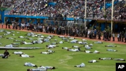 FILE - Performers re-enact events at a ceremony to mark the 20th anniversary of the Rwandan genocide, at Amahoro stadium in Kigali, Rwanda, April 7, 2014.
