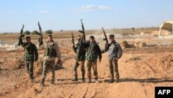 A group of Syrian pro-government forces raise their guns in celebration on the outskirts of Kweyris near the Kweyris military air base, east of the Syrian province of Aleppo, Nov. 10, 2015.