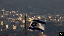 Bendera Israel berkibar di depan desa Majdal Shams, Dataran Tinggi Golan yang dikuasai Israel, 11 Oktober 2018. (Foto: dok)
