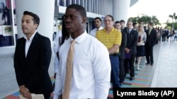 FILE - Luis Mendez, left, a student at Miami Dade College, left, and Maurice Mike, a student at Florida International University, wait in line at a job fair held by the Miami Marlins, at Marlins Park in Miami in 2013.