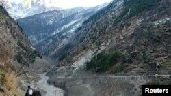 ຜູ້ຄົນຍ່າງຜ່ານເຂືຶ່ອນທີ່ຖືກທຳລາຍ ຫຼັງຈາກແທ່ງນ້ຳກ້ອນ ເທິງພູຫິມະໄລແຕກອອກ ແລະໄຫຼຊຸລົງມາ ເຮັດໃຫ້ເຂື່ອນພັງ ທີ່ບ້ານ Raini Chak Lata ໃນເຂດເມືອງ Chamoli ລັດ Uttarakhand ປະເທດອິນເດຍ ເມື່ອວັນທີ 7 ກຸມພາ 2021. REUTERS/Stringer NO ARCHIVES. NO RESALES.