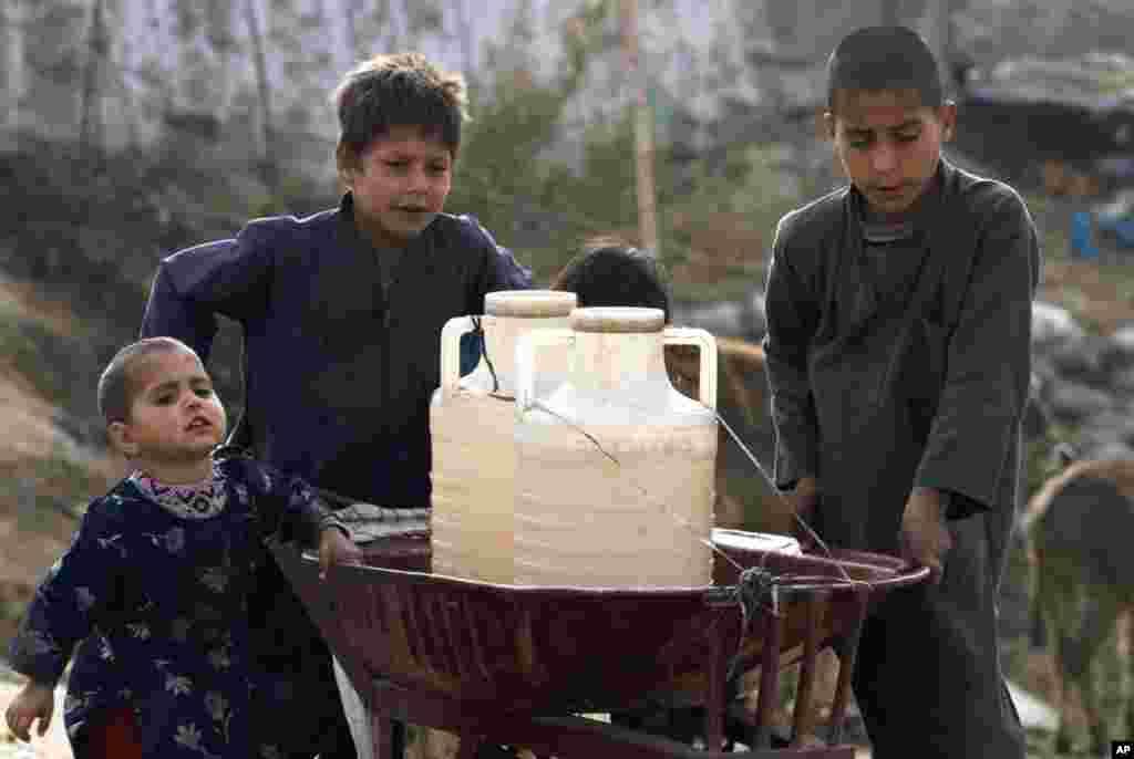 Những bé trai Pakistan chất các vại nước trên một xe cút kít mang về nhà sau khi bơm tay lấy nước ở vùng ngoại ô Islamabad vào ngày 21/3. (AP)