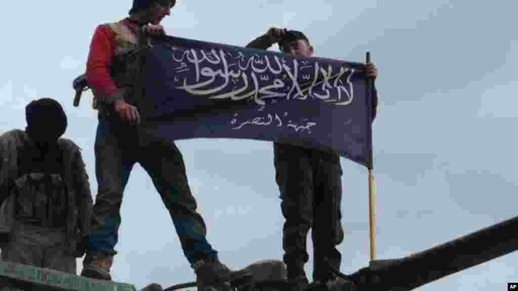 Rebels from al-Qaida affiliated Jabhat al-Nusra waving their brigade flag