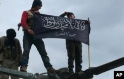FILE - Rebels from al-Qaida-affiliated Jabhat al-Nusra, also known as the Nusra Front, wave their brigade flag, as they step on the top of a Syrian air force helicopter at Taftanaz air base that was captured by the rebels in Idlib province, northern Syria, Jan. 11, 2013.