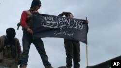 Rebels from al-Qaida affiliated Jabhat al-Nusra are pictured waving their brigade flag. As many as 500 Turks have been recruited since al-Nusra was formed in January 2012. (AP Photo/Edlib News Network)