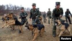 Binh sĩ Bắc Triều Tiên và chó nghiệp vụ trong cuộc tập trận tại một địa điểm bí mật. Ảnh do Thông tấn xã KCNA phát hành ngày 6/4/2013.