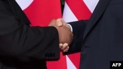 도널드 트럼프 미국 대통령(오른쪽)과 김정은 북한 국무위원장이 12일 싱가포르 카펠라 호텔에서 열린 미북 정상회담에서 악수하고 있다.