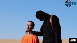 An image grab taken from a video released by the Islamic State (IS) and identified by private terrorism monitor SITE Intelligence Group purportedly shows British aid worker David Haines dressed in orange and on his knees in a desert landscape speaking to