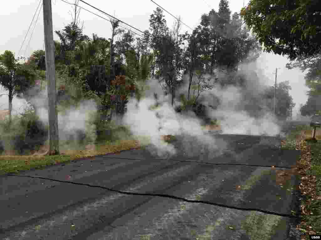 Steam rises from fissure 9 on Moku Street in the Leilani Estates Subdivision, Hawaii, May 7, 2018. HVO scientists on the scene reported hearing rumbling noises in the area.