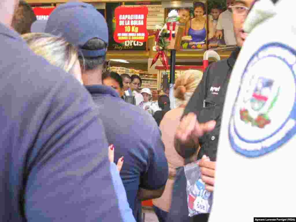 En algunos locales de Caracas la policía participa en la organización y entrega de números para poder ingresar al automercado.