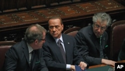 """Italian Prime Minister Silvio Berlusconi (C) holds and saves a memo reading """"308 [the result of the vote] - 8 traitors - political reversal - vote - take note: resign - Republic President - a solution"""" during a budget vote at the parliament in Rome, Novem"""